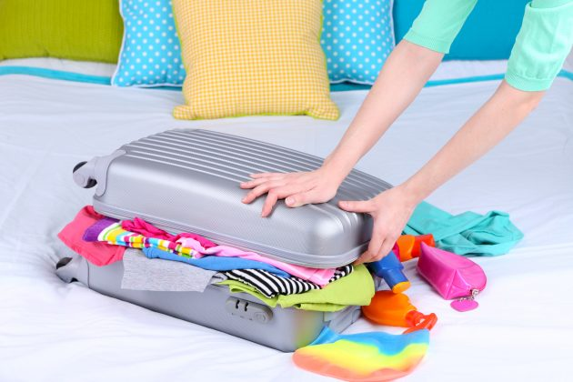 Girl collects suitcase on bed close-up