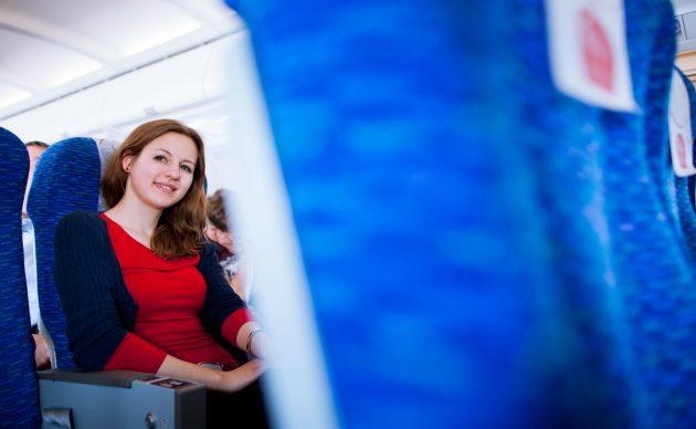Pretty young female passenger on board of an aircraft (color ton