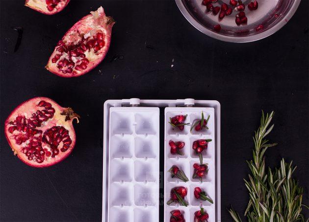 Гранатовый коктейль с шампанским и розмарином: распределите листики розмарина и зёрна граната по формочкам для льда