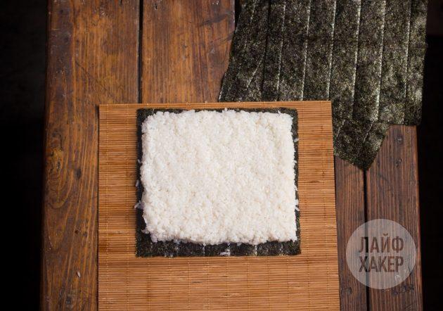 Как приготовить суширрито: расположите лист нори на коврике и покройте его слоем риса