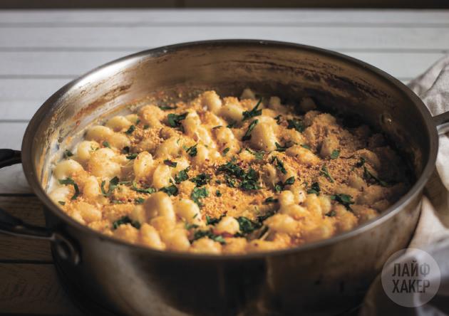 Посыпьте макароны с сыром сверху хлебными крошками, петрушкой