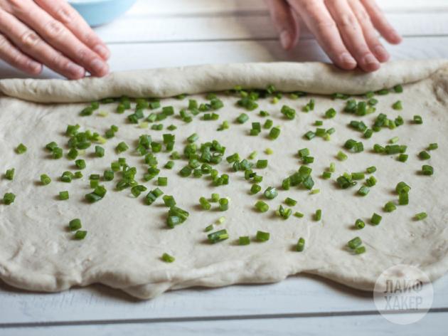 Как приготовить китайские паровые булочки: посыпьте поверхность нарезанным зелёным луком и сверните пласт в рулет