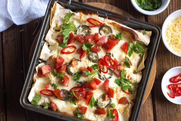 Посыпьте готовую энчиладу с курицей помидорами, острым перцем и зеленью