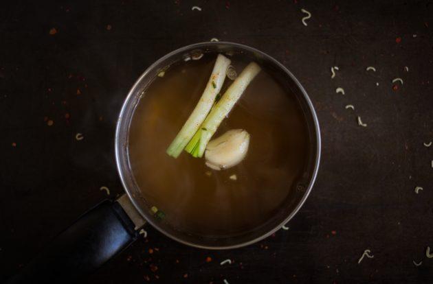 Как приготовить домашний рамен: доведите бульон докипения и положите внего зубчик чеснока, очищенный имбирь и стебли зелёного лука