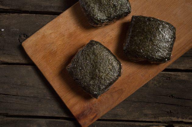 Плотно оберните онигирадзу пищевой плёнкой, придавая суши-сэндвичу квадратную форму