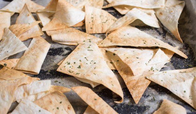 Греческая закуска из баклажанов: выложите кусочки лаваша одним слоем на лист пергамента и подсушите 5–7 минут