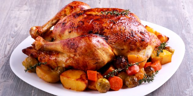 Целая курица на подушке из овощей в духовке