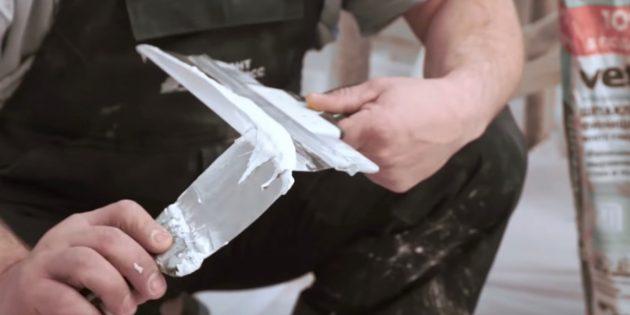Как выровнять стены шпаклёвкой: маленьким шпателем наберите немного шпаклёвки и нанесите её на край широкого шпателя
