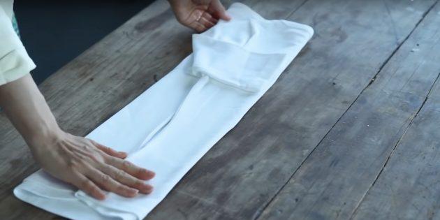Загните к середине правую часть футболки и сложите рукав