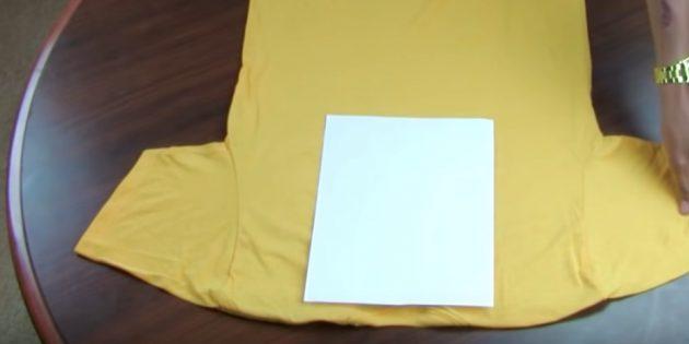 Положите футболку спинкой вверх и посередине поместите бумагу