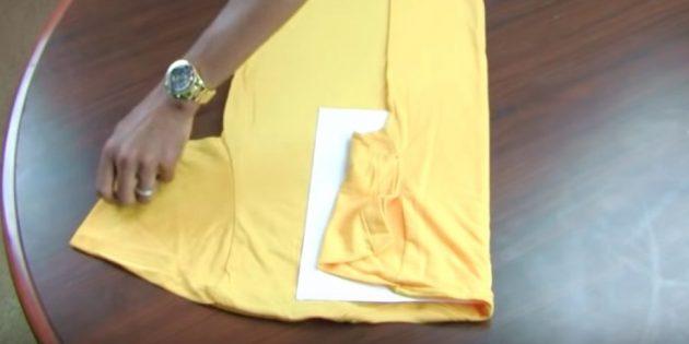 Сверните одну сторону футболки по краю листа и подогните рукав