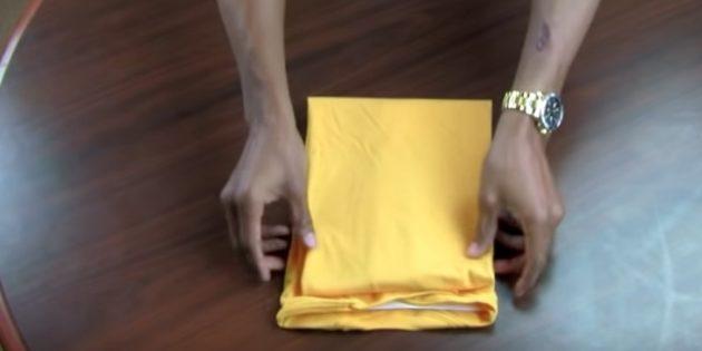 Сложите футболку пополам по краю бумаги