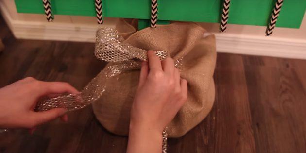 Поставьте ёлку, обмотайте подставку мешковиной и обвяжите лентой