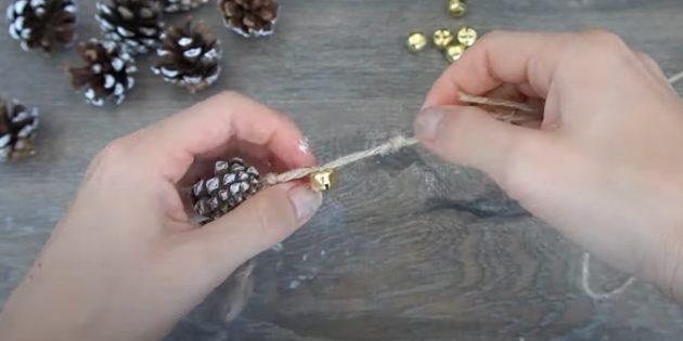 Новогодние поделки из шишек: закрепите колокольчик на шпагате