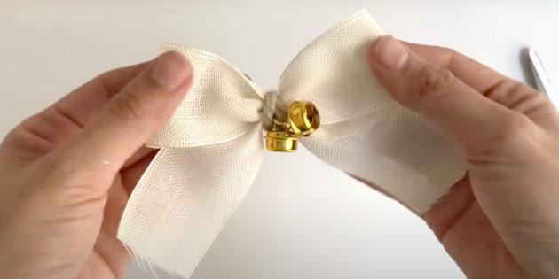 Новогодние поделки из шишек: закрепите колокольчике на банте