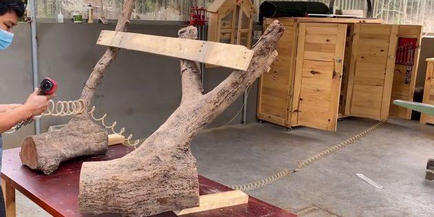 Как сделать скамейку своими руками: поставьте две детали с ветками на стол или другую ровную поверхность и примерьте их, временно соединив между собой доской на гвоздях