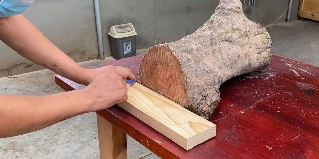 Как сделать скамейку своими руками: положите кусок ровной доски на стол, придвиньте к стволу и начертите линии
