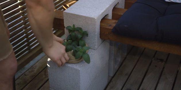 Как сделать скамейку своими руками: в оставшиеся отверстия боковых блоков вставьте по вазону с цветами или травами.