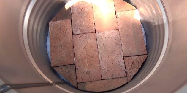 Постелите внутрь два слоя утеплителя и насухо уложите первый ряд кирпича