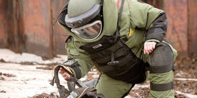 Сапёр в защитном костюме EOD обезвреживает противопехотную мину