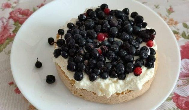 Выложите на бисквит крем и ягоды